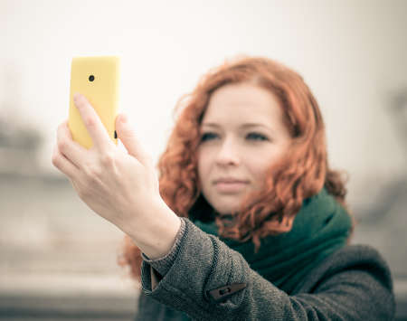 Young redhead girl taking a selfie outdoors  Color toned image  photo