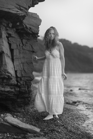 twiggy:  Beautiful young woman goes along the coast. Black and white image.