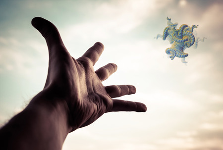 Extend:   Hand of a man reaching to the fractal figure in sky. Selective focus on hand. Stock Photo