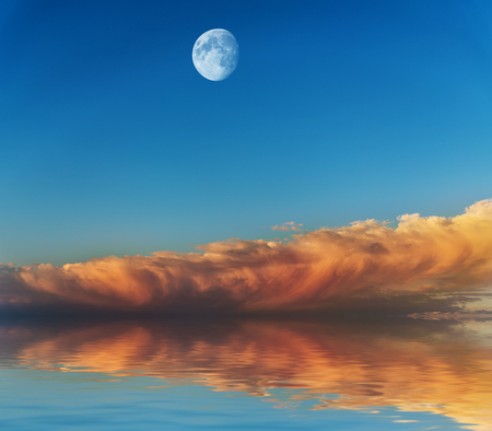 Moon with sunset sky reflected in water surface. photo