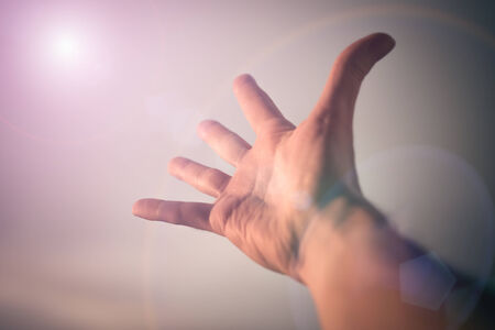 Hand of a man reaching to towards sky. Color toned image. Stock Photo