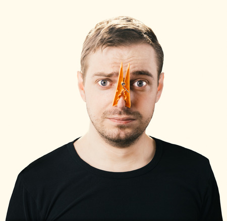 Portrait of caucasian man with orange clothespin on his nose - bad smell concept photography. Color toned image. photo