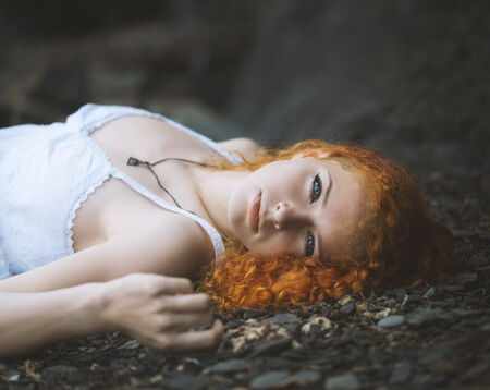 well laid: Redhead woman at the rocky beach in a white dress laid down on the gravel. Color toned image.