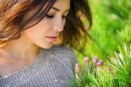 Beautiful brunette touches needles on the spruce. Close-up. Shallow depth of field. photo