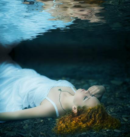 pelirrojas: Pelirroja hermosa mujer joven que miente bajo el agua. Foto de archivo