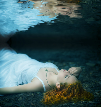 drown: Young redhead beautiful woman lying underwater. Stock Photo