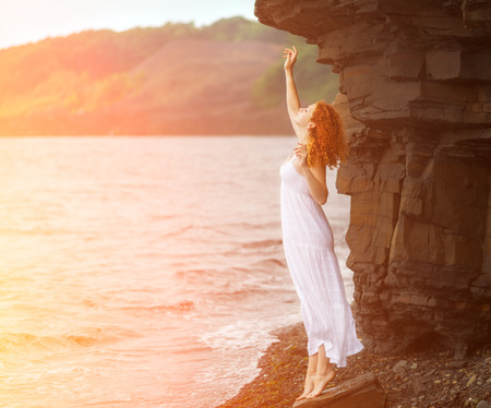 Redhead woman in white dress standing on beach and looking to somewhere. With sunshine effect.