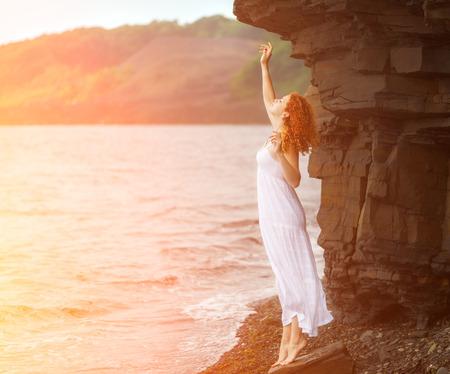 Rothaarige Frau im weißen Kleid auf Strand steht und auf der Suche nach irgendwo. Bei Sonnenschein Wirkung. Standard-Bild - 33611819