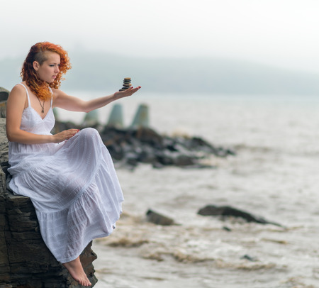 Portrait of redhead woman holding zen stones in hand with sea background in foggy day. Soft focus.