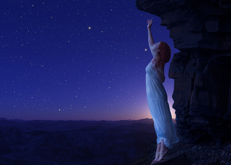 blue stars: Young woman standing on cliff Stock Photo