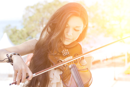 Portrait of a young female playing the violin. With sunshine. Color toned image. 스톡 콘텐츠