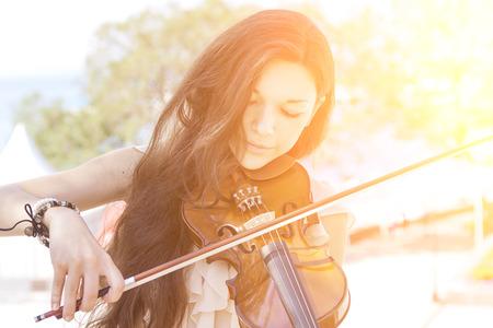 orquesta: Retrato de una mujer joven tocando el viol�n. Con sol. Imagen en tonos de color.