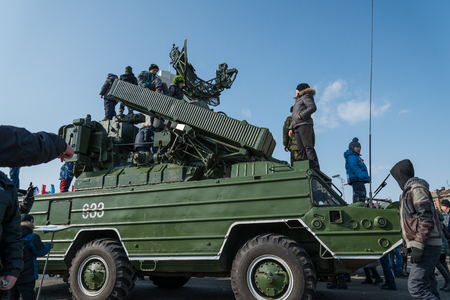 defender: VLADIVOSTOK, RUSSIA - FEBRUARY 23, 2015: Children play on modern russian armored vehicle during festivities devoted to Defender of the Fatherland Day.