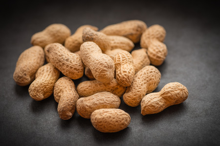 Natural looking roasted peanuts on a dark background. photo