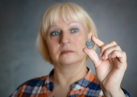 pennies: Woman holding coin on grey background. Selective focus. Stock Photo