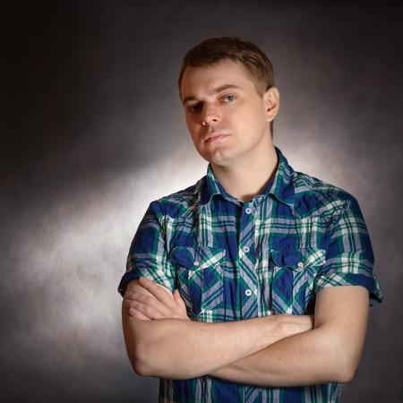 despondent: Sad young man, portrait on the dark background.