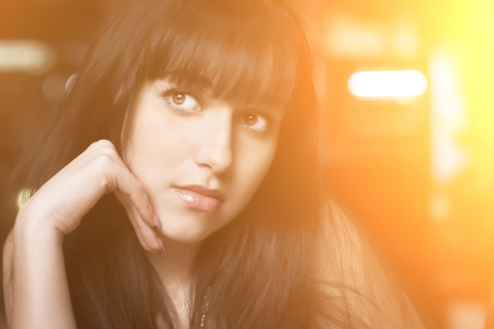 dreary: Young beautiful brunette woman. Closeup portrait with sunshine effect.