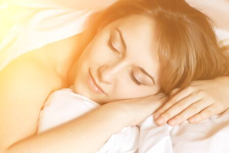 Closeup portrait of a beautiful young lady sleeps on the bed with sunshine effect. photo
