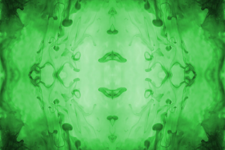 green ink: Green ink forming patterns resembling Rorschach Test ink blots.