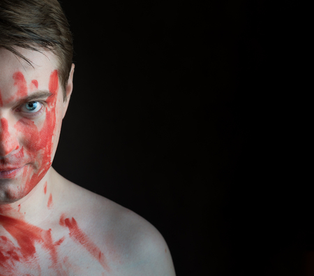 merciless: Portrait of young man with blood on his face on dark background.