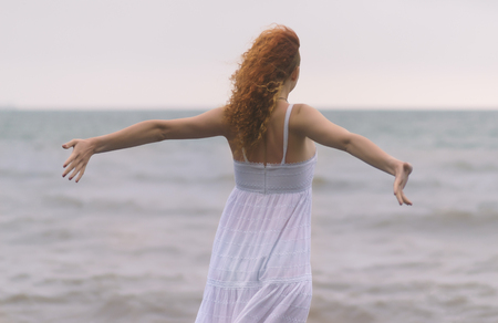 Young redhead woman spread her hands on the beach in foggy day. Stock Photo