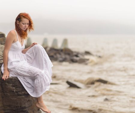 on the black sea: Redhead woman sitting on the coast on beach and looks into the distance at sea. Selective soft focus.