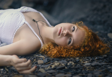 well laid: Beautiful redhead woman at the rocky beach in a white dress laid down on the gravel. Stock Photo
