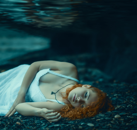 murder scene: Young redhead beautiful woman lying underwater. Stock Photo