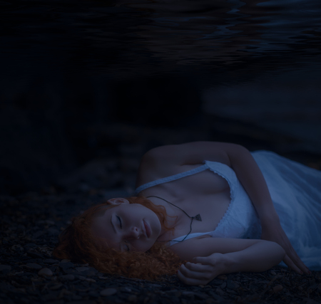 Young redhead beautiful woman lying underwater. Stock fotó