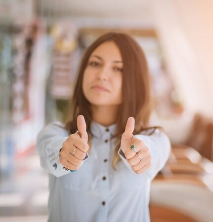 executive woman: Happy young businesswoman giving thumbs up. Selective focus. Stock Photo