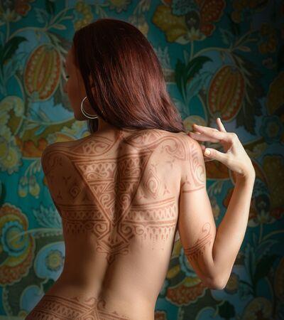 tatouage sexy: Belle femme avec un tatouage sur son dos.