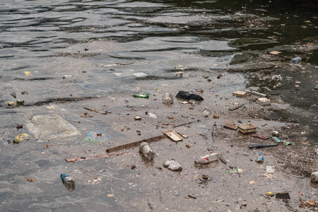 Oil and garbage pollution in the water. Selective focus with shallow depth of field.