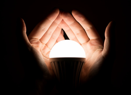手は、光る led ランプをカバーします。 写真素材