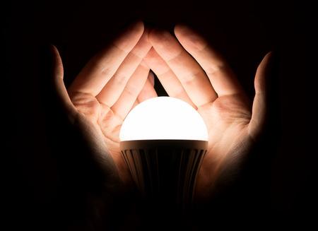 Mani coprono incandescente lampada led. Archivio Fotografico - 44173236