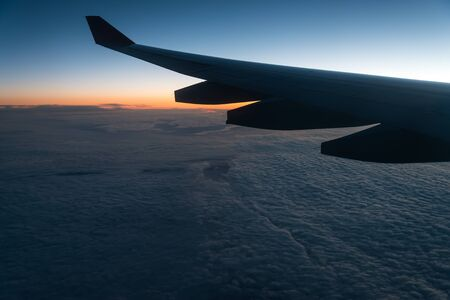 km: Wing of a airplane at sunrise at an altitude of 11 km.