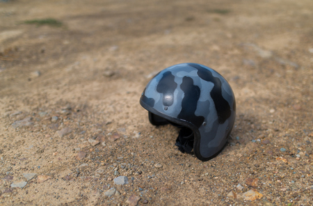 special steel: Scratched helmet on ground. Selective focus.