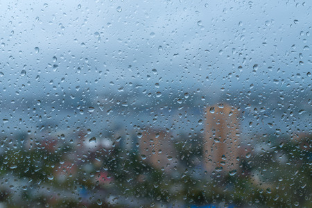 Drops on a glass with cityscape on background. Stock Photo