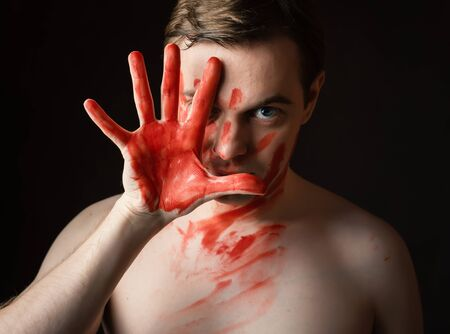 merciless: Portrait of young man with blood on his face and palm on dark background. Stock Photo