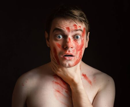 constricted: Young man with blood on his face hold himself for the neck. Stock Photo