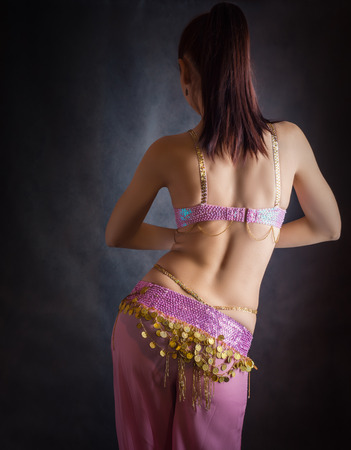 Exotic belly dancer woman with perfect body on a dark background. Stock Photo