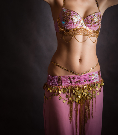 costume jewelry: Exotic belly dancer woman with perfect body on a dark background. Stock Photo