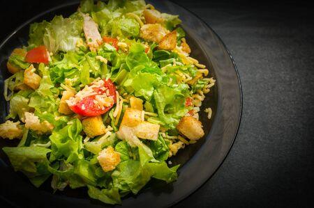 lite food: Caesar salad made of fresh vegetables on dark background. Selective focus.