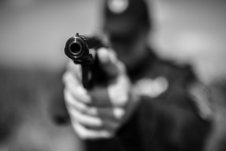 carabineer: Detail of a police officer holding gun. Selective focus with shallow depth of field. Black and white toning.