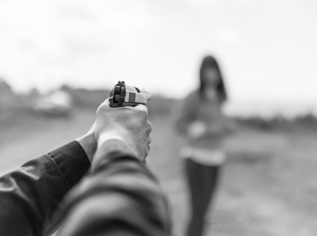 male killer: Man hand holding gun aim to woman. Selective focus with shallow depth of field. Black and white toning.