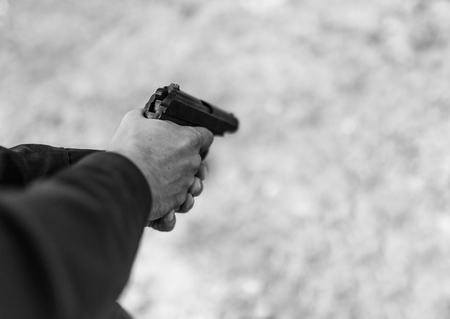 Man hand holding gun. Selective focus with shallow depth of field. Black and white toning.