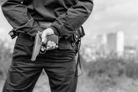 Detail of a police officer holding gun. Selective focus with shallow depth of field. Black and white toning.