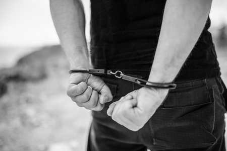 A mens hands in handcuffs behind his back. Selective focus with shallow depth of field. Black and white toning.