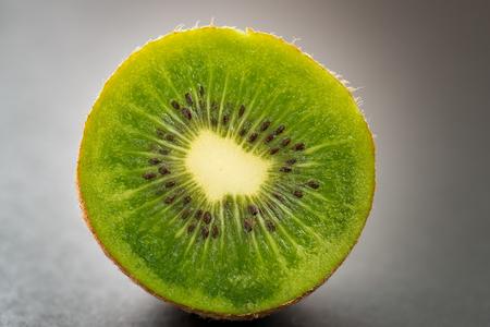 sappy: Ripe kiwi fruit, half full on dark background. Selective focus with shallow depth of field. Stock Photo