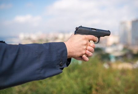 male killer: Man hand holding gun. Selective focus with shallow depth of field. Stock Photo