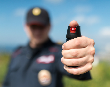 man with gun: Detail of a police officer holding pepper spray. Selective focus with shallow depth of field. Stock Photo
